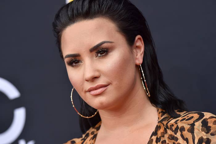 Demi posing on a red carpet in a leopard-print outfit and hoop earrings