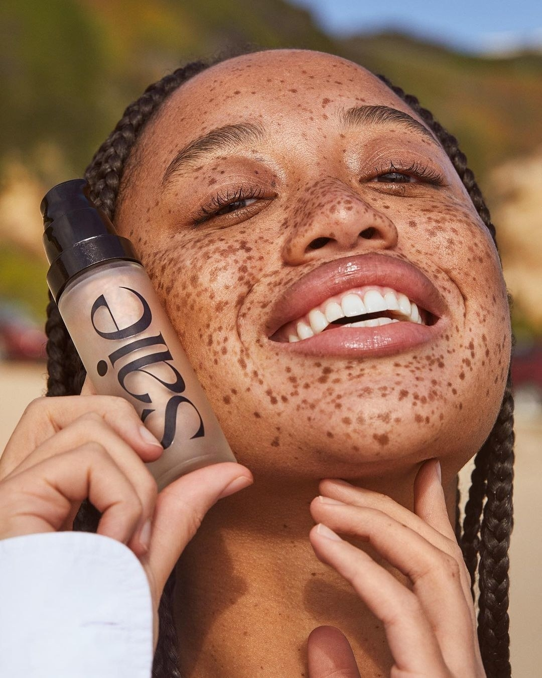 A smiling person holding a bottle of the gel highlighter next to their face; they are glowing and happy