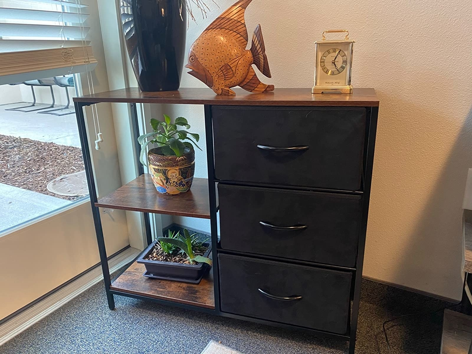 reviewer image of the rustic brown kamiler storage dresser with plants on the bottom two tiers and a vase on the top surface