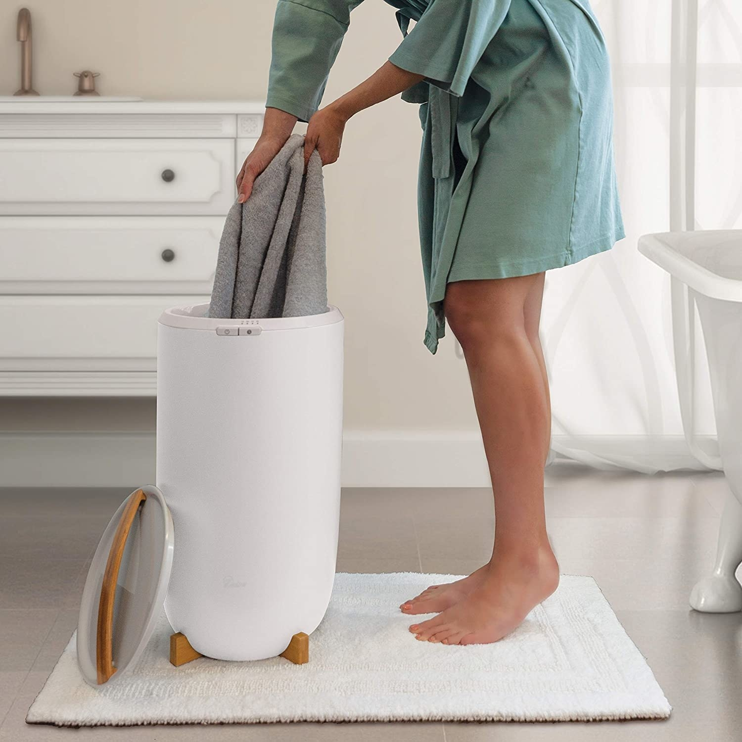 A person taking a towel our of the warmer