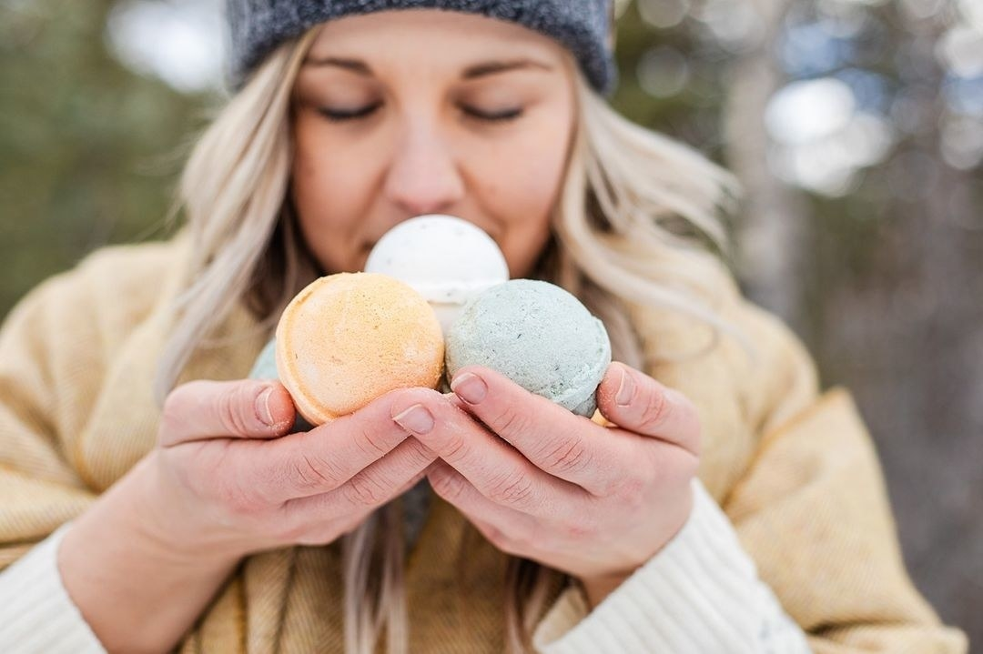A person smelling a trio of bath bombs that they're holding in their hands