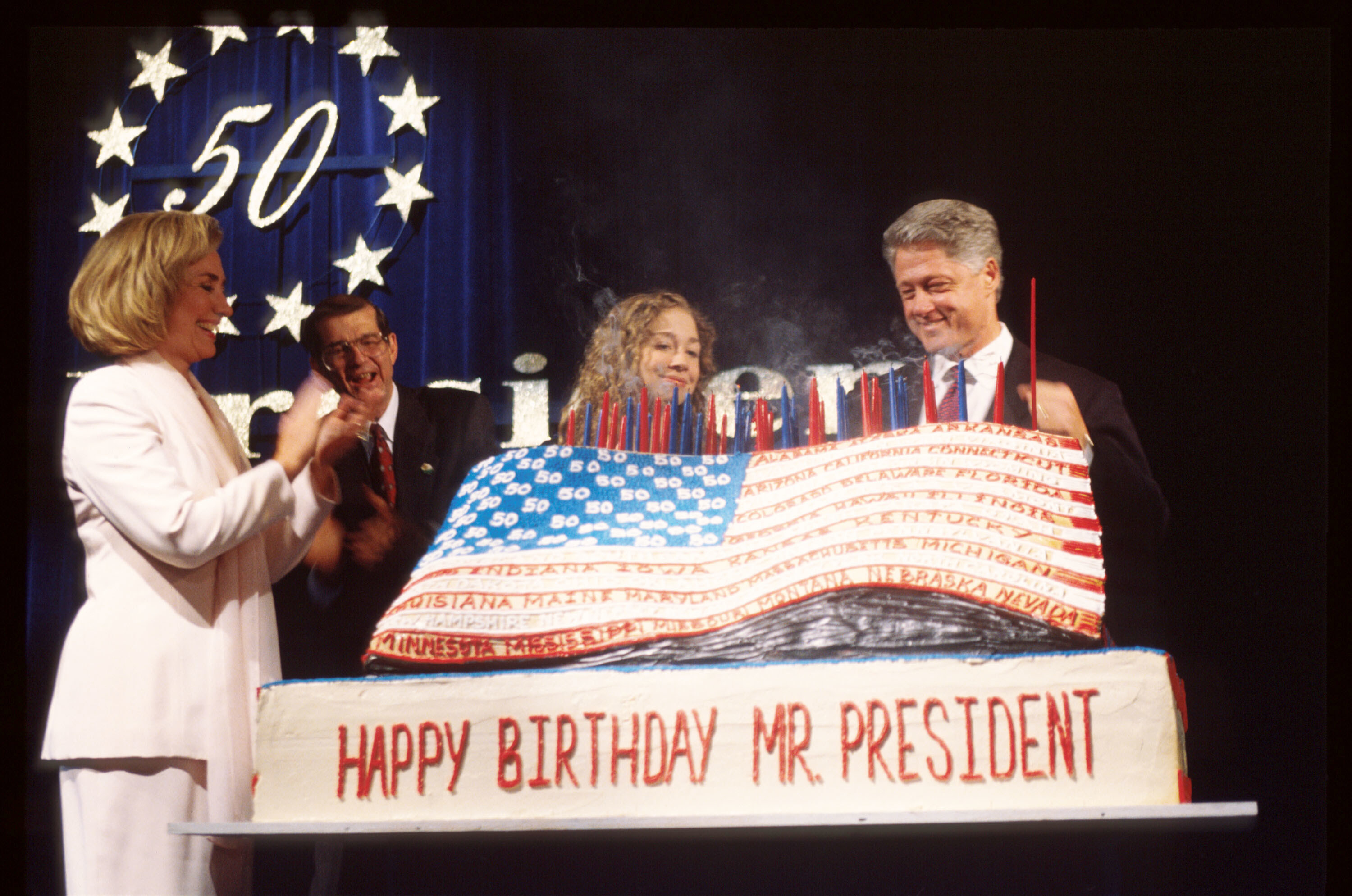 The Clinton family standing around a giant American flag cake