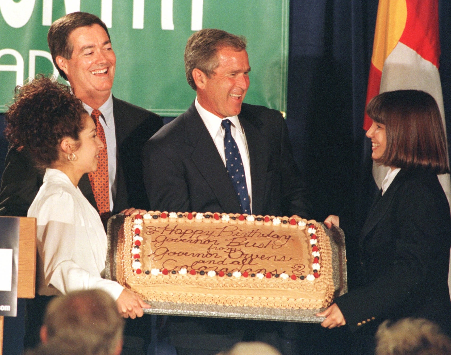George Bush on stage with two women in front of him holding a birthday cake