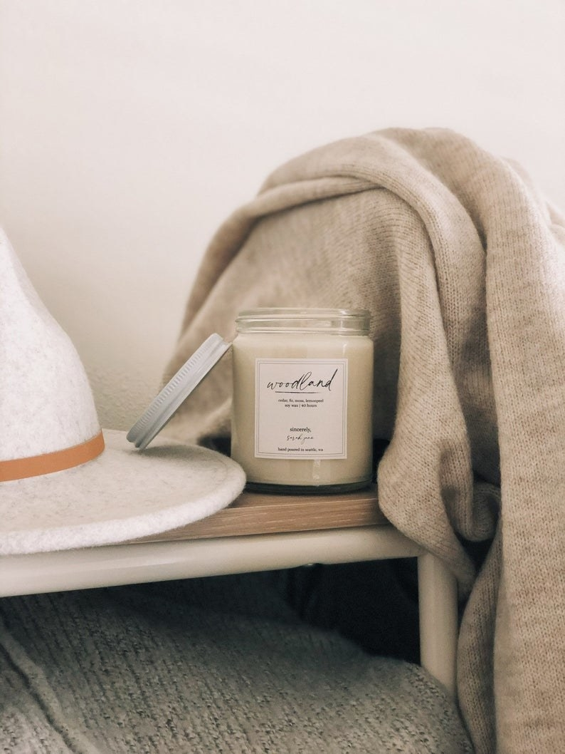 """White candle with a white label that says """"woodland"""" in black cursive"""