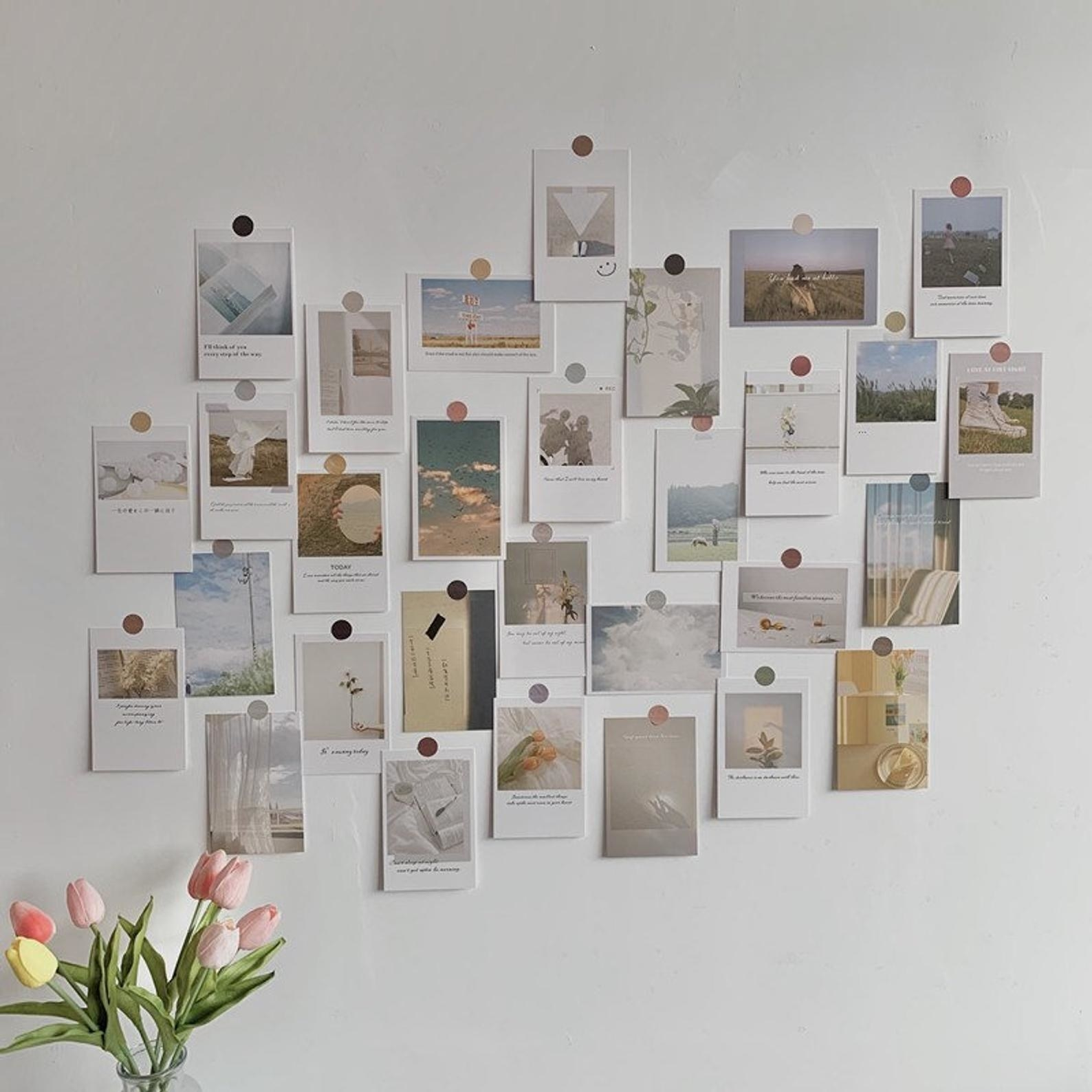 A series of rectangular muted photos and prints stuck to a wall with circular stickers