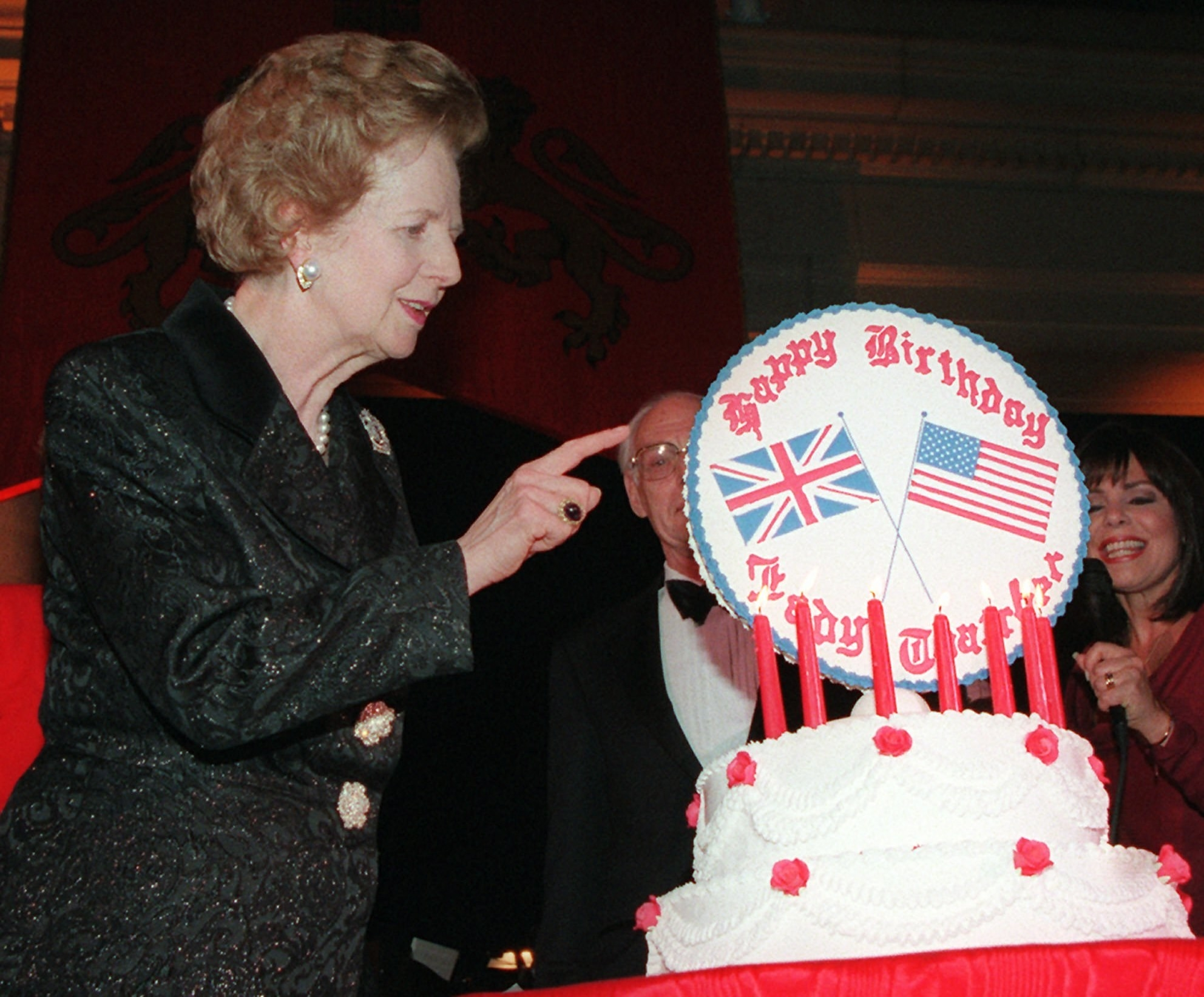 Margaret Thatcher looking at a cake with american and british flags