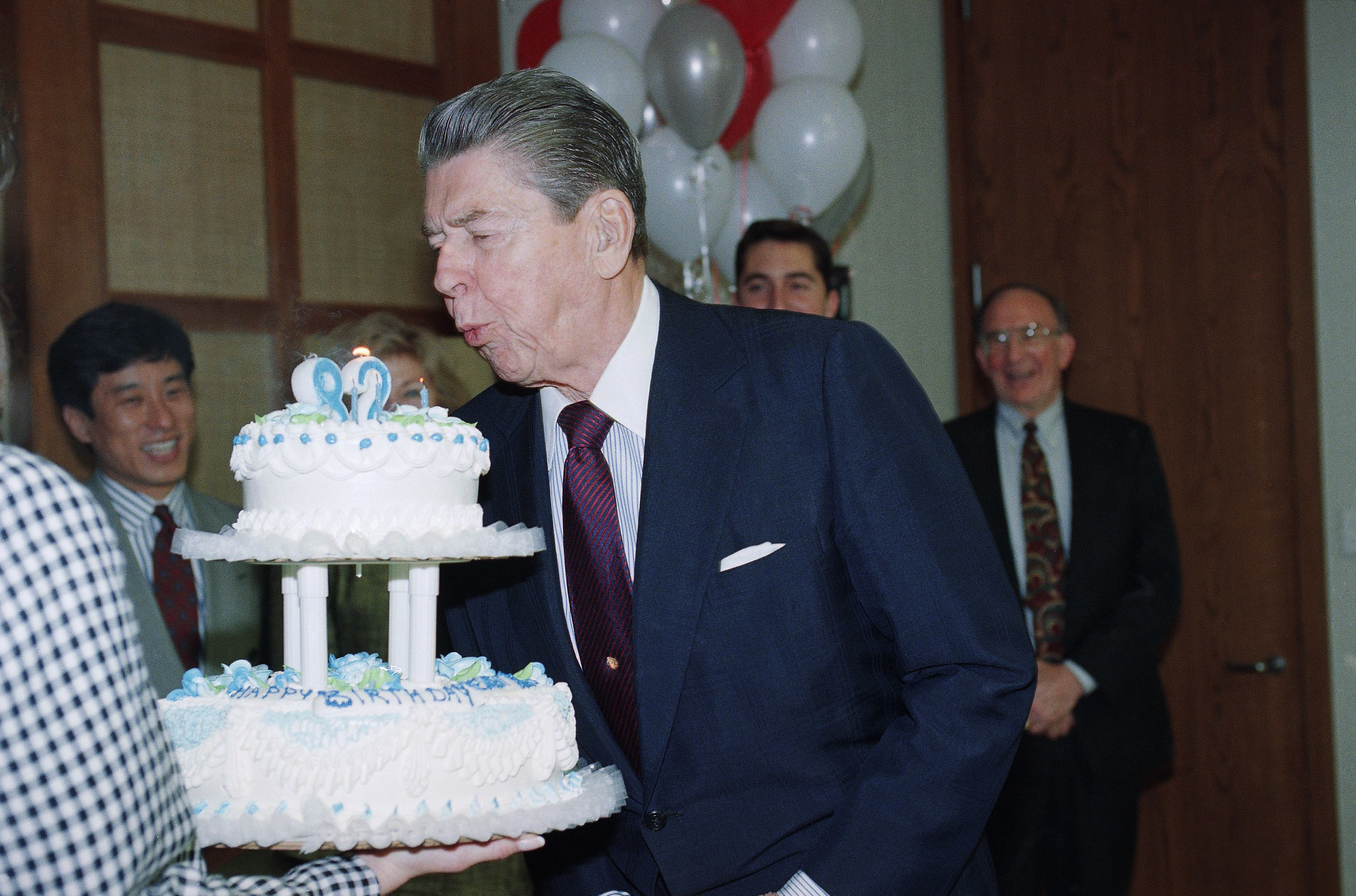 Ronald Reagan blows out a two-tier birthday cake