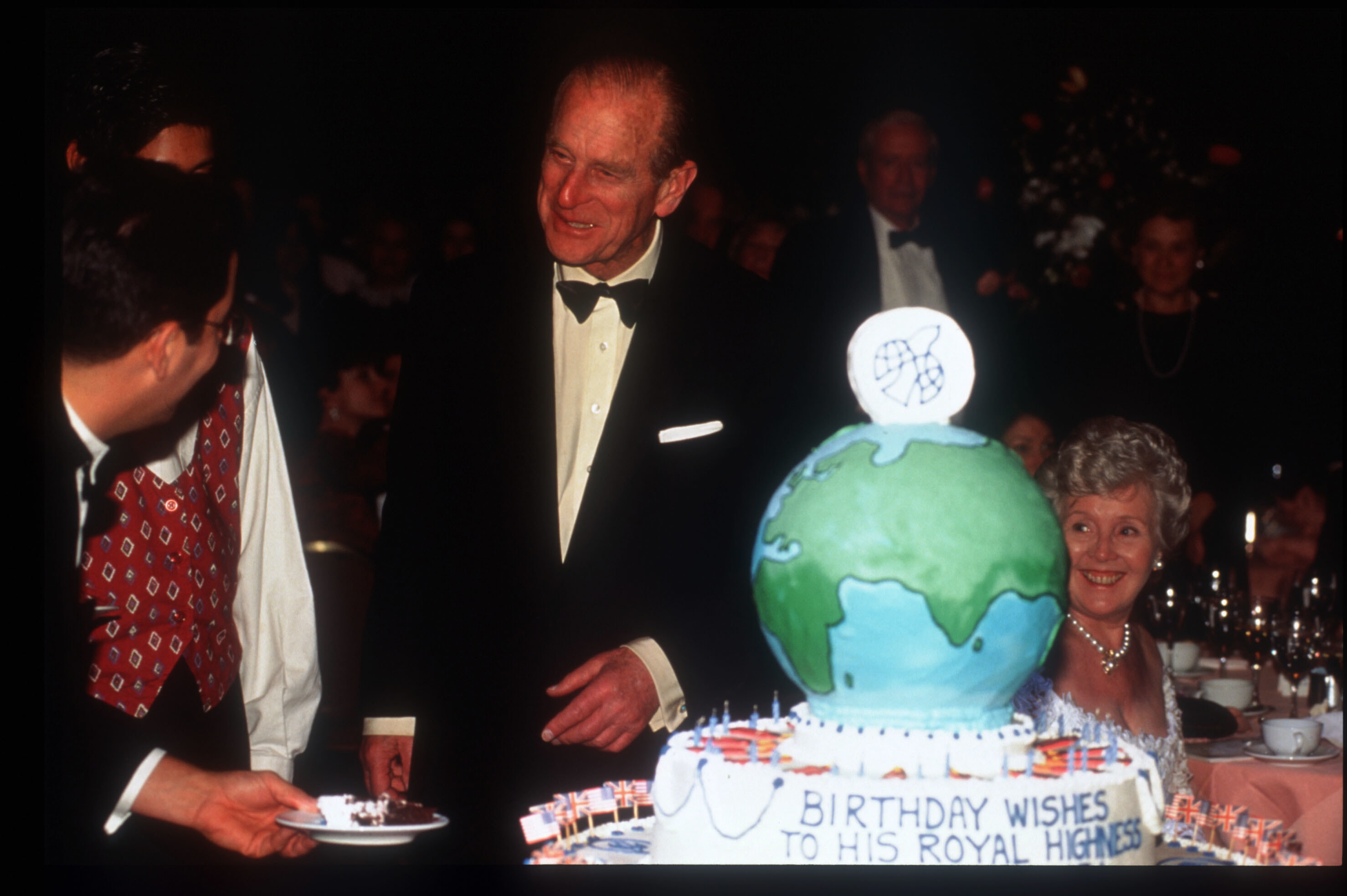 Prince Philip, in a tuxedo, stands behind a cake shaped like a globe