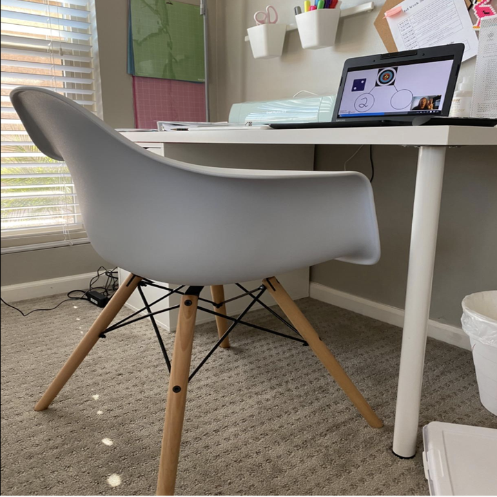 White office chair with four light brown legs in front of desk