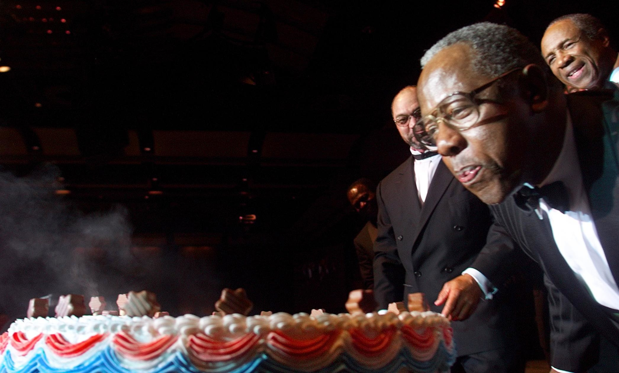 Hank Aaron blows out candles on his birthday in a tuxedo