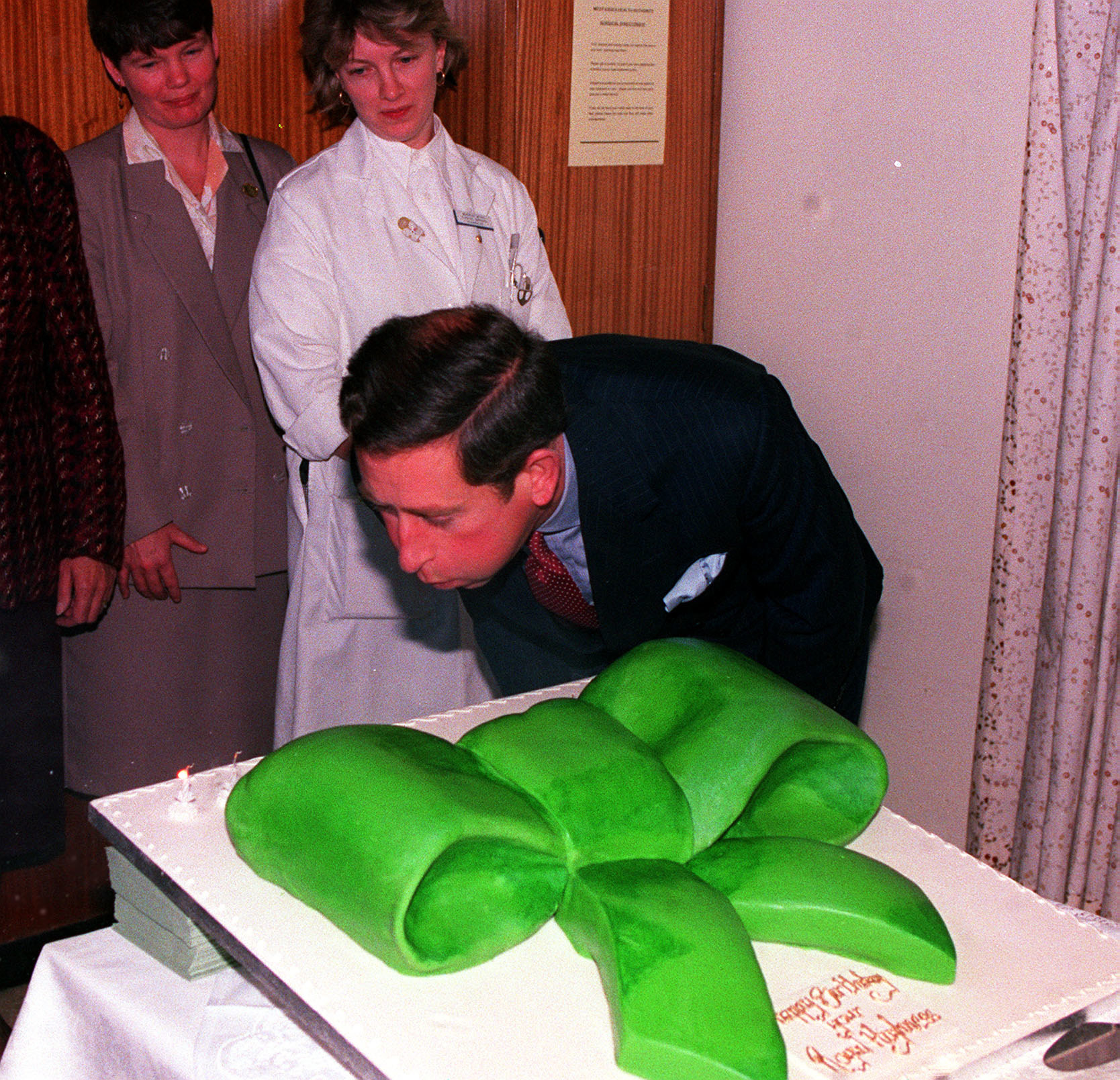 Prince Charles blowing out candles on a cake with an enormous green bow