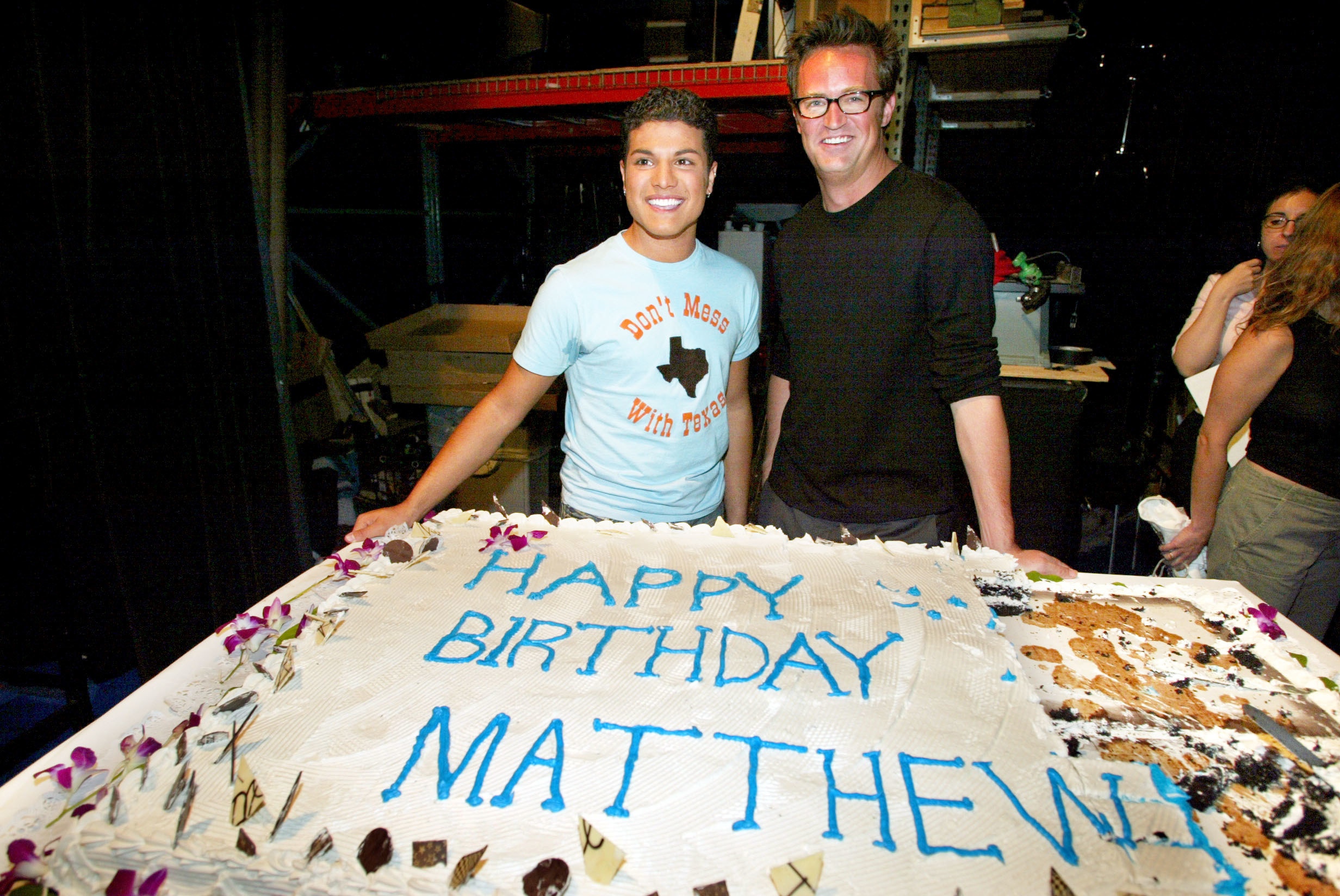 Matthew Perry poses by a giant sheet cake that reads Happy Birthday Matthew