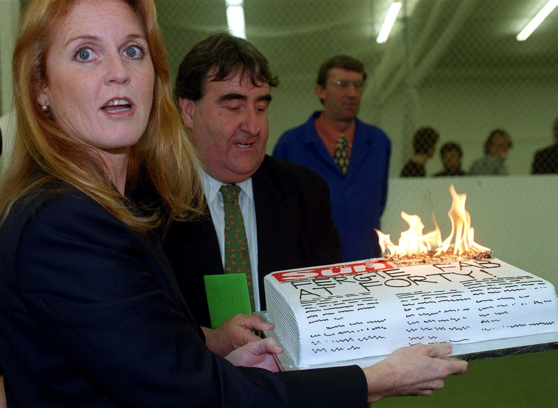 Duchess of York holding a cake shaped like a newspaper that's on fire