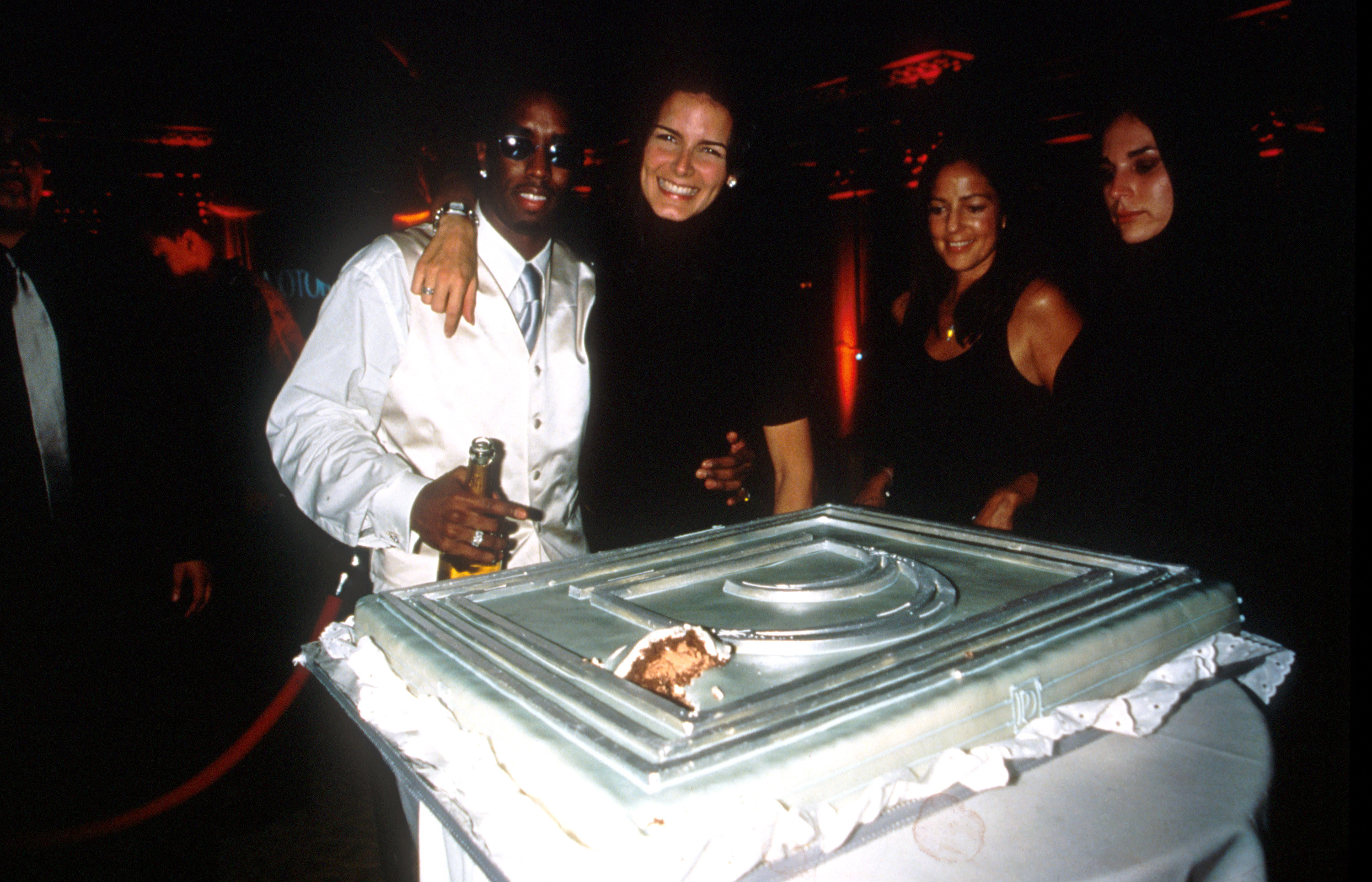 Diddy and Angie Harmon pose by a silver birthday cake