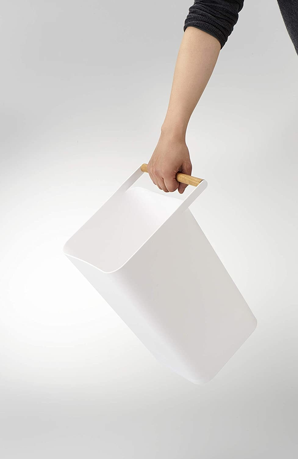 A white square shaped trashcan with a wooden handle on the lid
