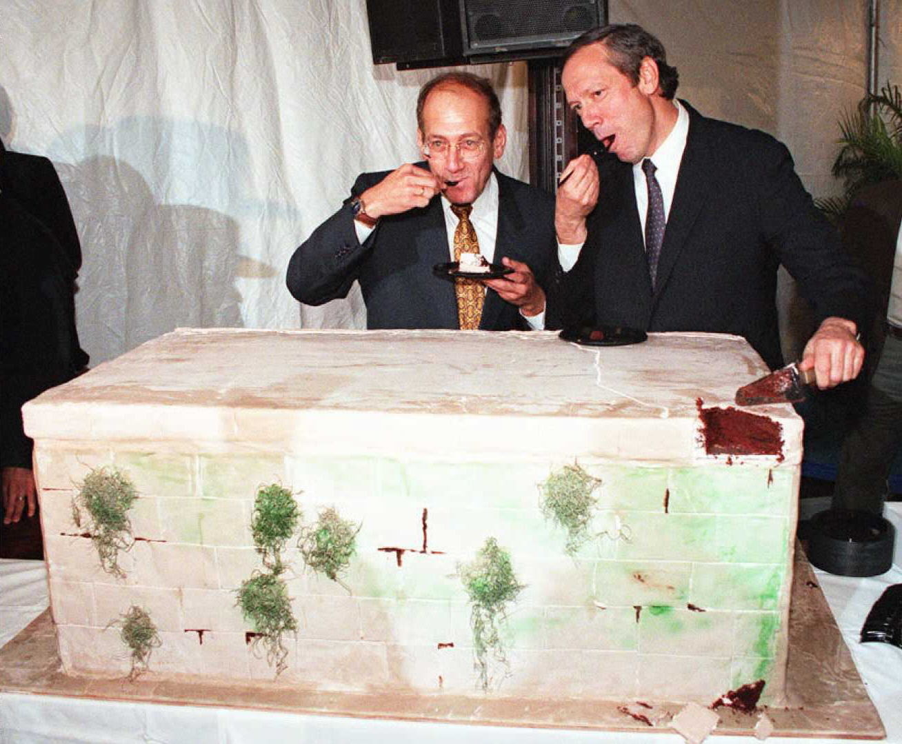 Two men eating bites out of cake shaped like a wall