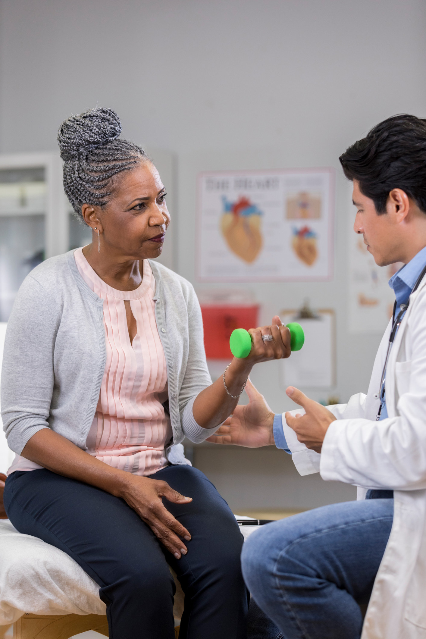 An older Black woman flexing her arm in front of a doctor