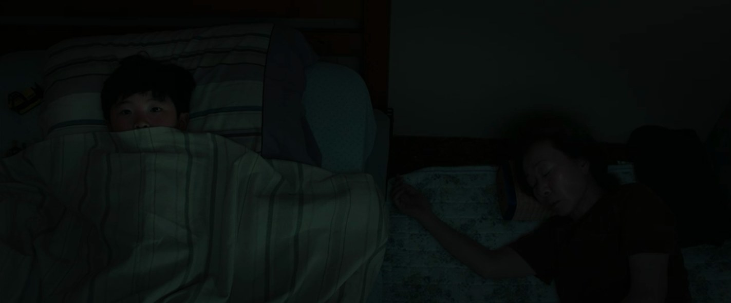 David lying on his bed in the dark with his blanket over his face, while his grandma sleeps on the floor directly to his left.