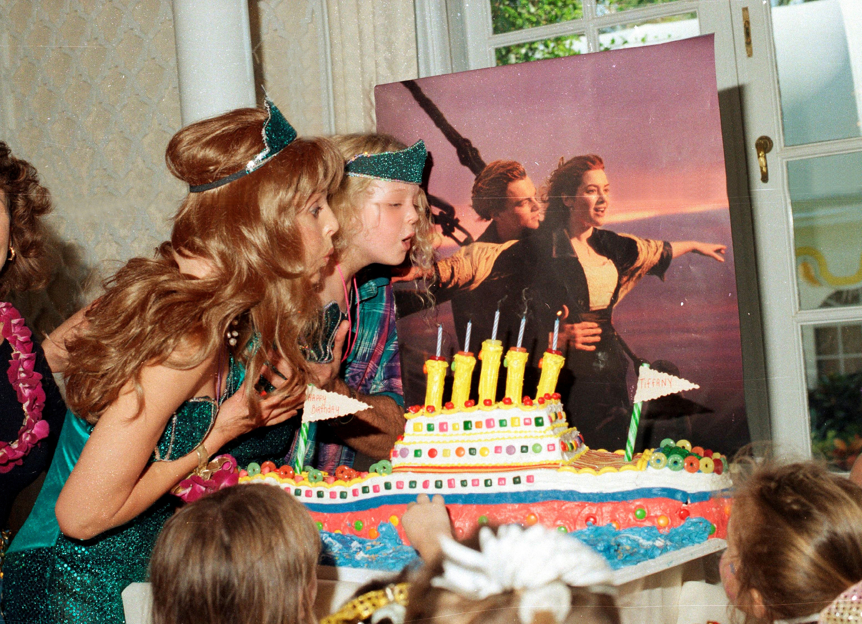 Marla Maples and Tiffany Trump blow out birthday candles on a cake shaped like a boat