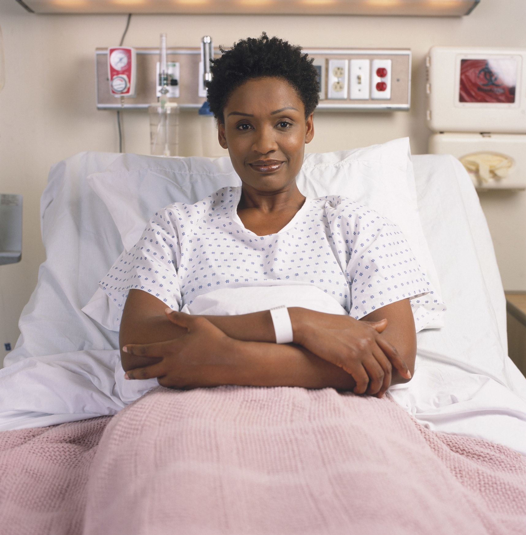 A Black woman sitting in a hospital bed