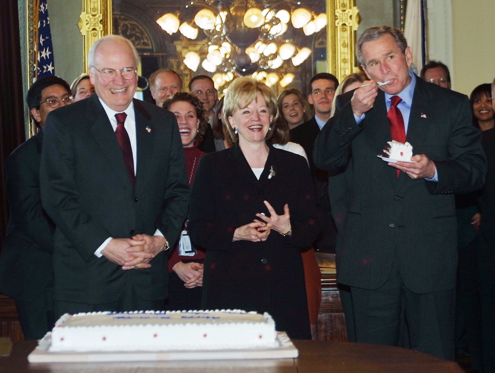 George Bush, right, eats a slice of cake in a room full of smiling people in suits
