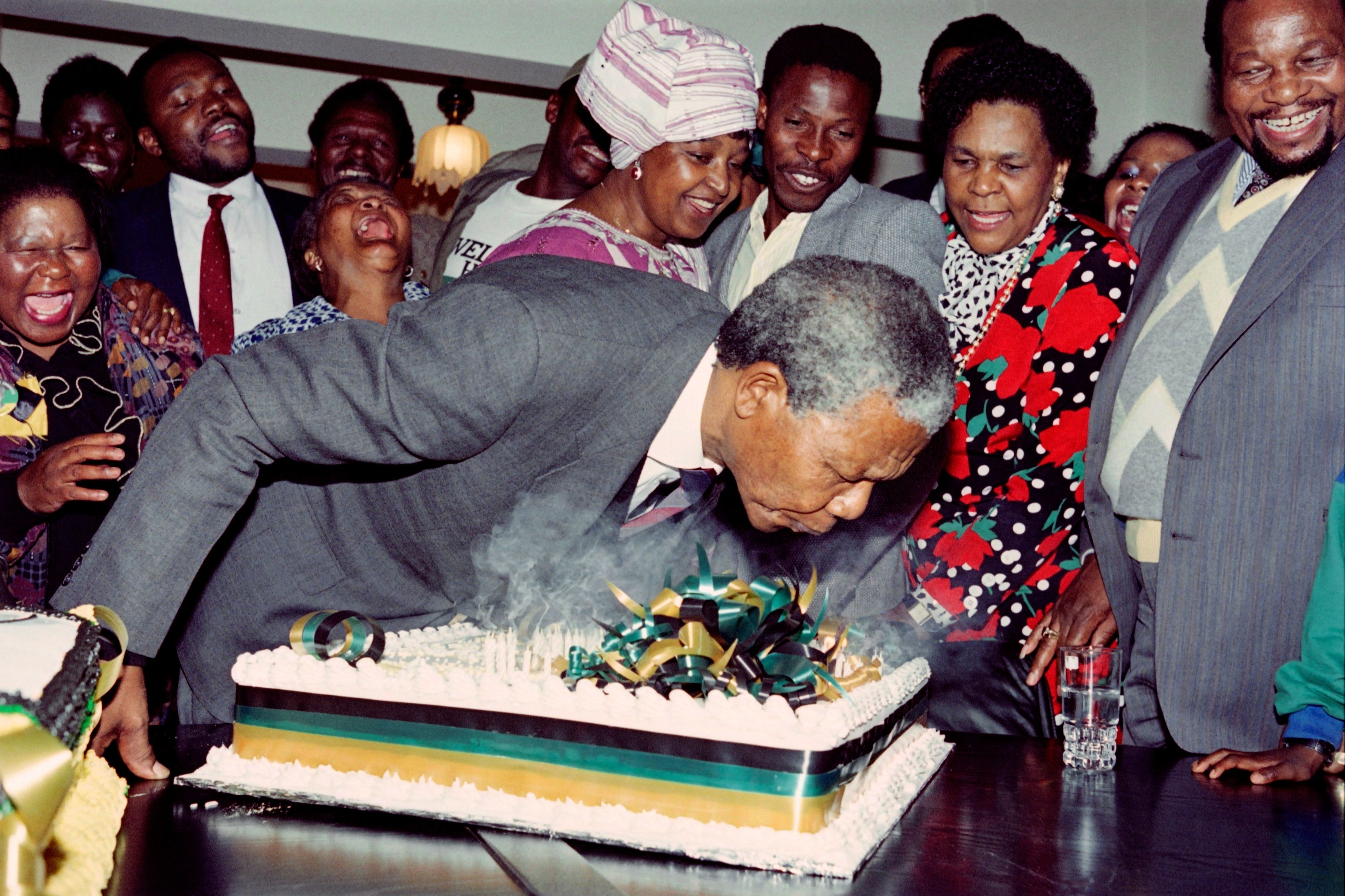 Nelson Mandela blows candles on his birthday cake surrounded by smiling people