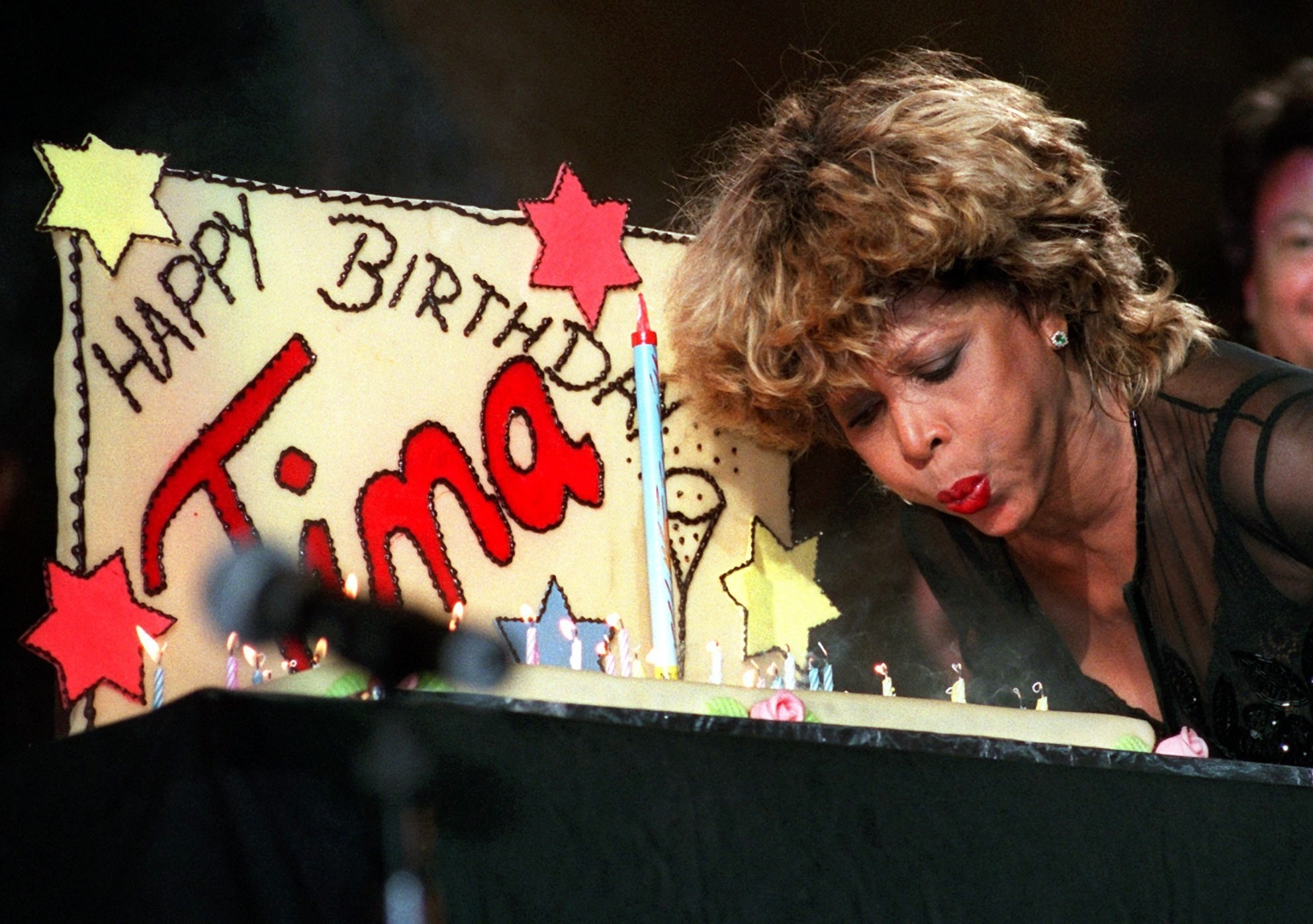 Tina Turner blows out a birthday cake that reads happy birthday tina