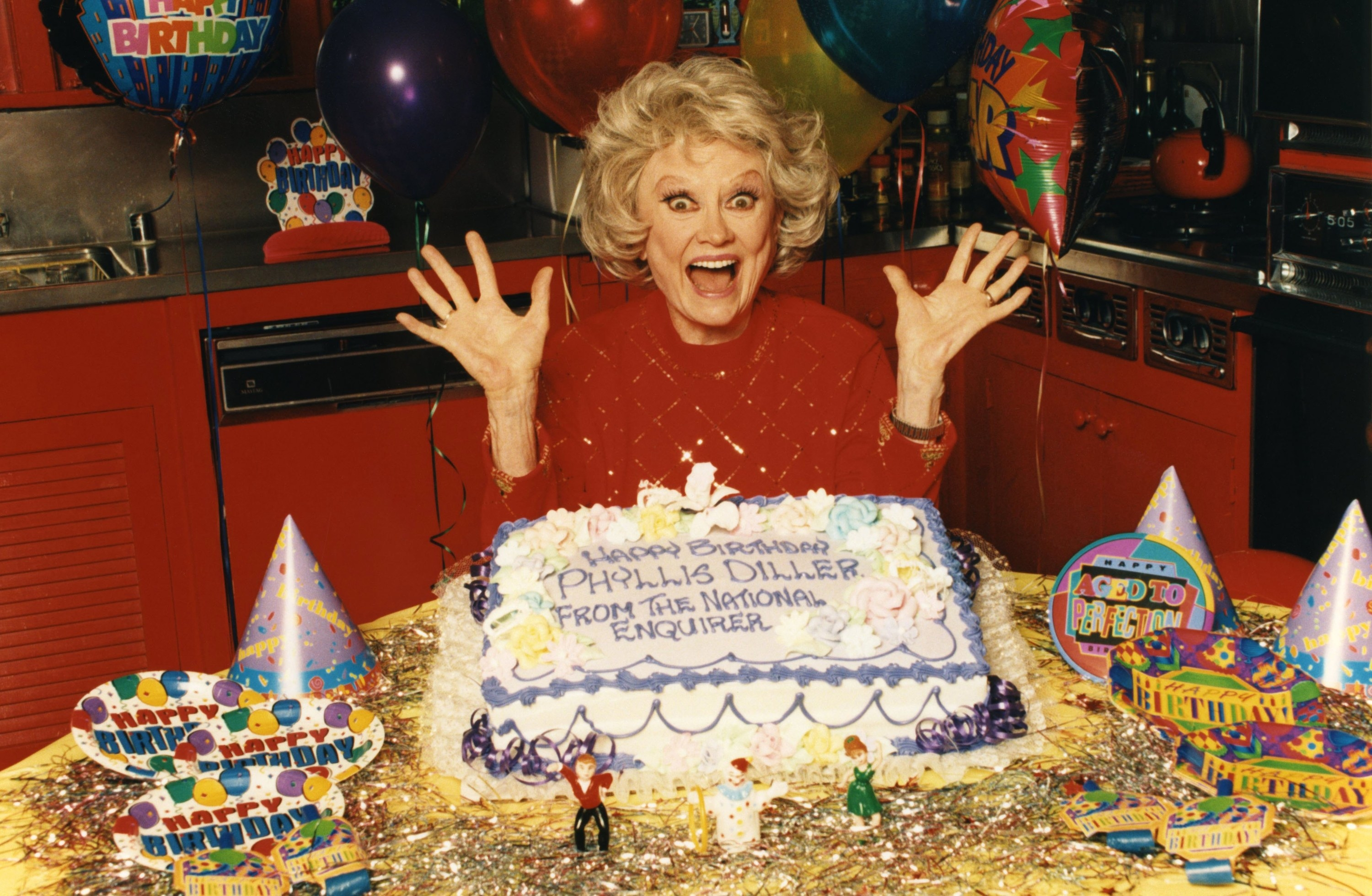 Phyllis Diller surrounded with birthday ephemera and the cake
