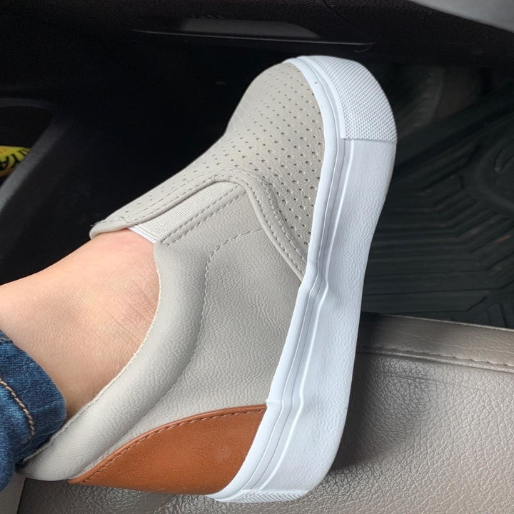 A reviewer photo of the profile view of someone wearing the slip-on sneakers in taupe with a brown leather patch on the back