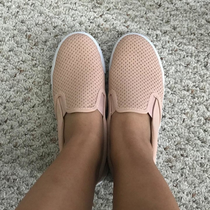 a reviewer photo of someone wearing the slip-on sneakers in pink