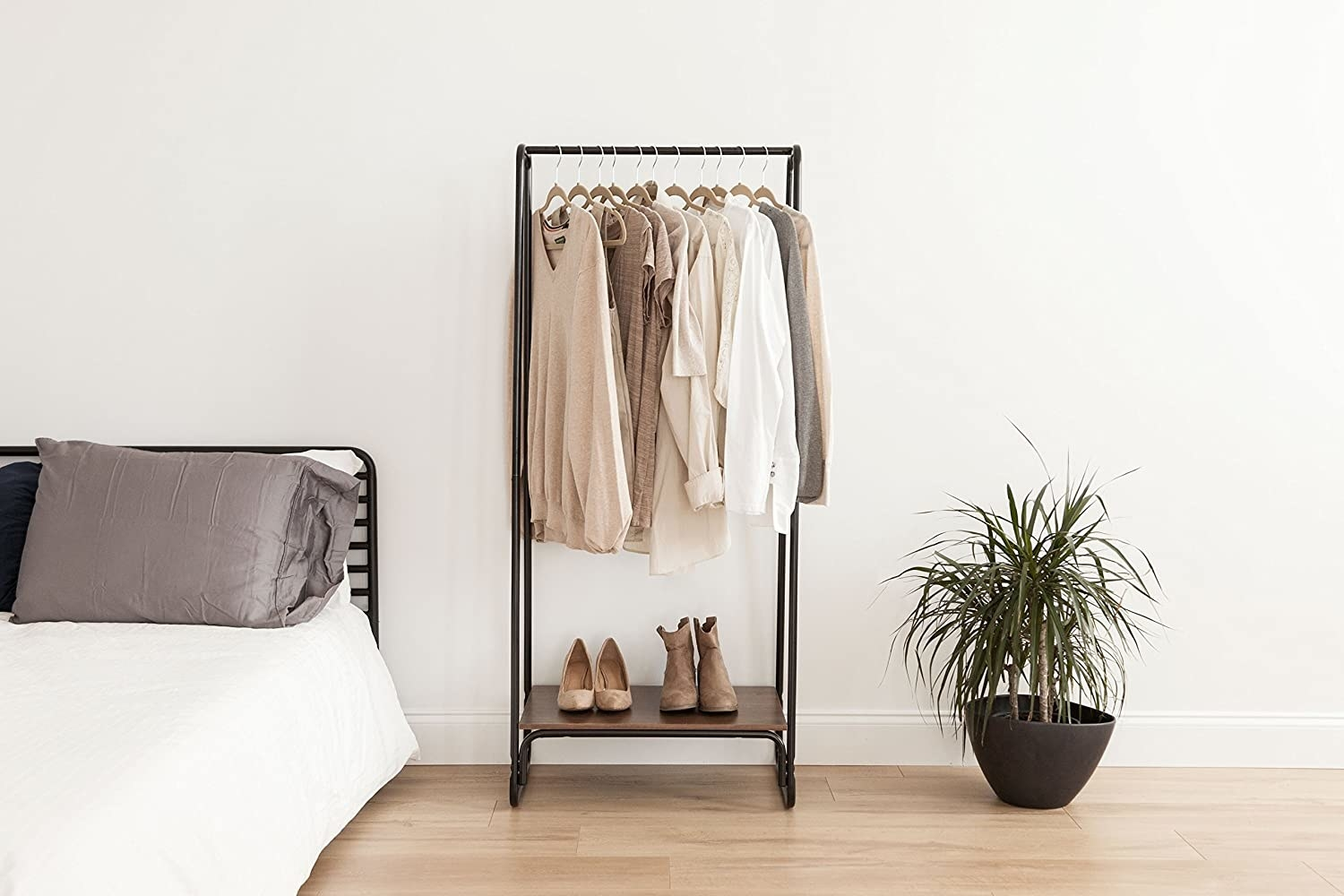 Simple metal garment rack with beige and white shirts hanging from it and small shelf for shoes below