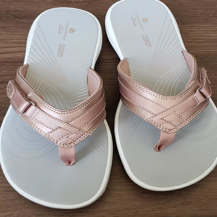a reviewer photo of a pair of flip-flops with rose gold straps