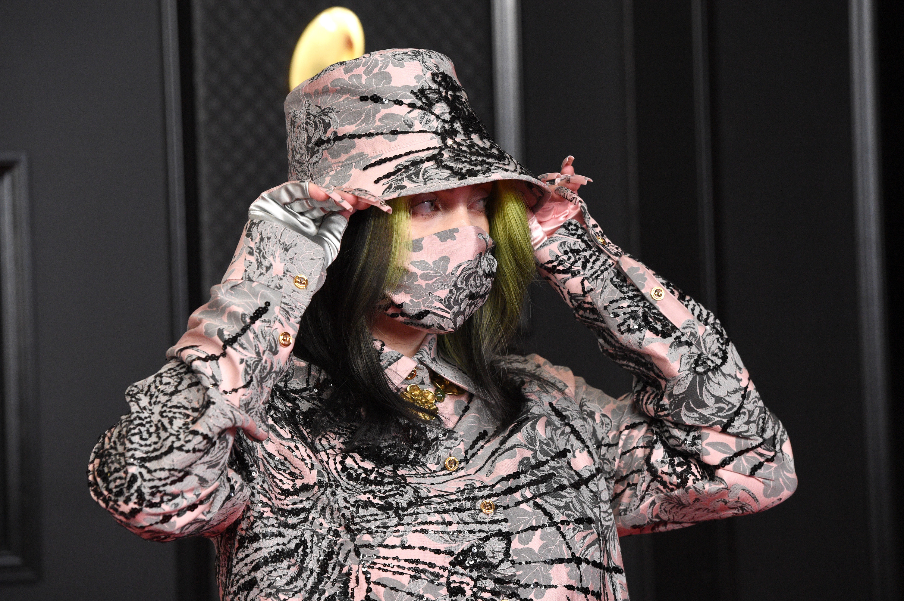 Billie wearing a matching pink, gray, and black print outfit, including brimmed hat and face mask