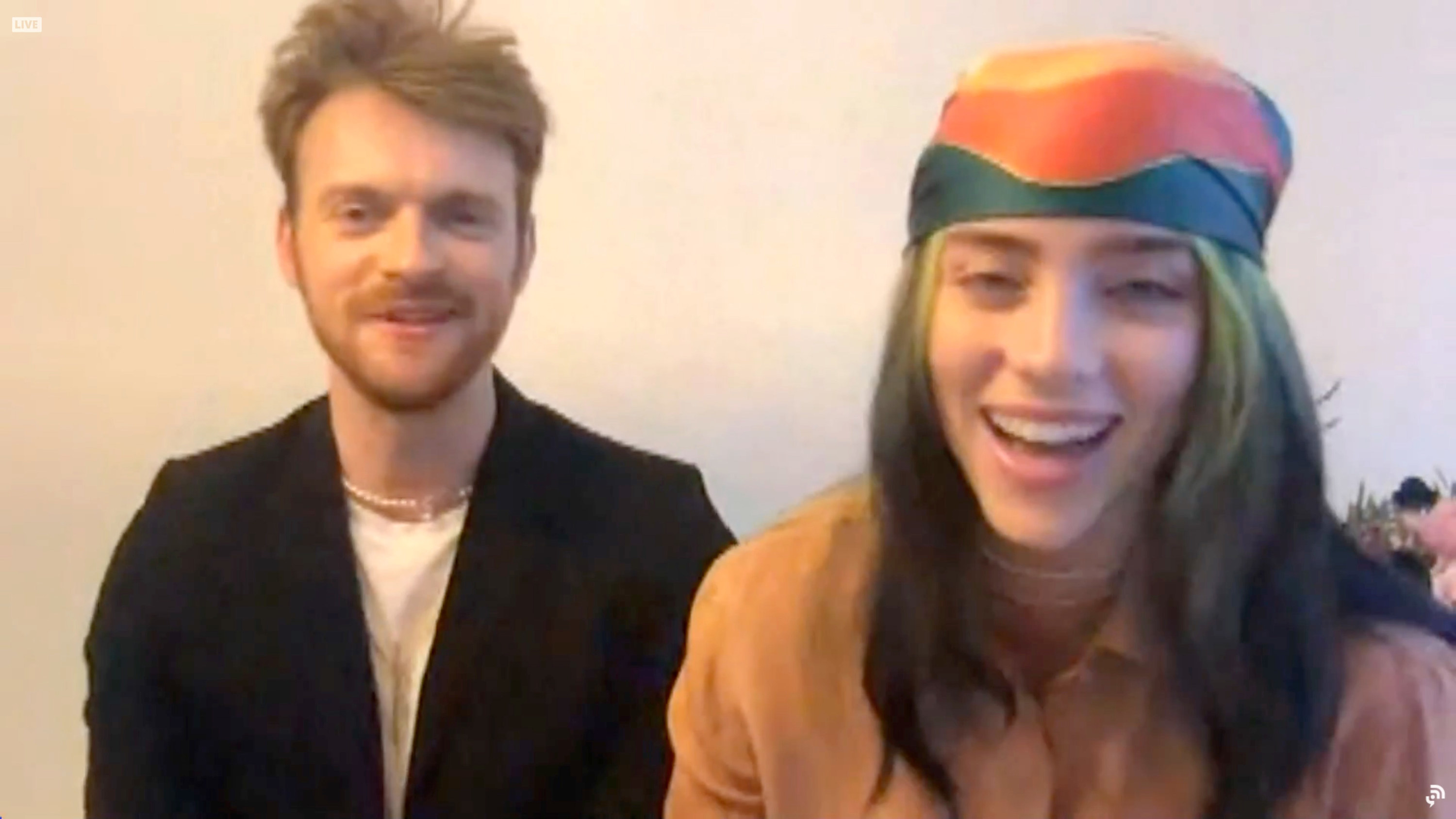 Billie, smiling, in a head wrap and sitting with her brother Finneas
