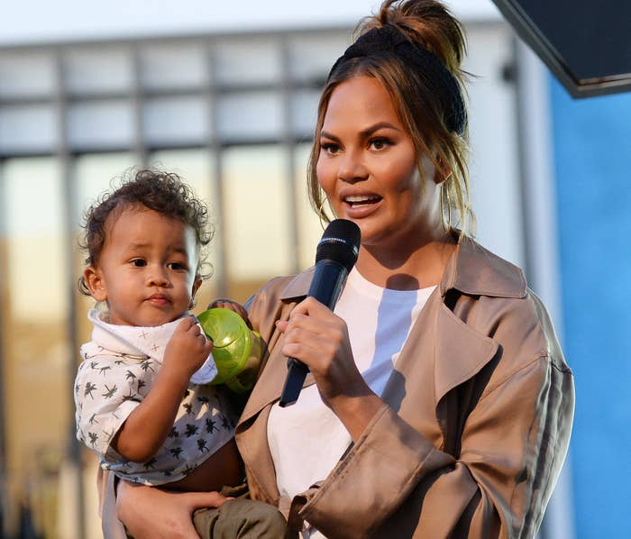 Chrissy holds her son Miles at an event