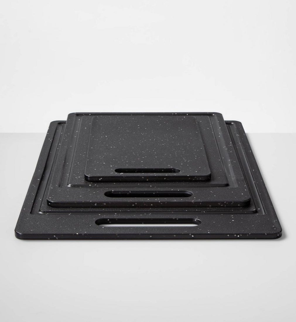 three different sized black with white speckles cutting boards with handles stacked on top of each other