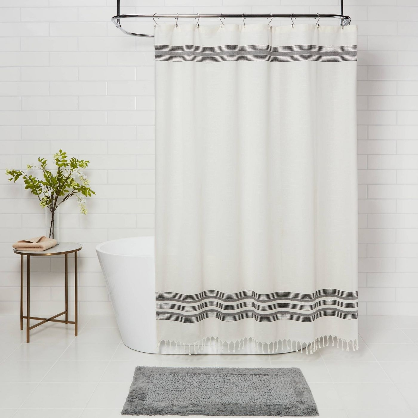 White shower curtain with dark grey stripes on the top and bottom and fringe along the bottom