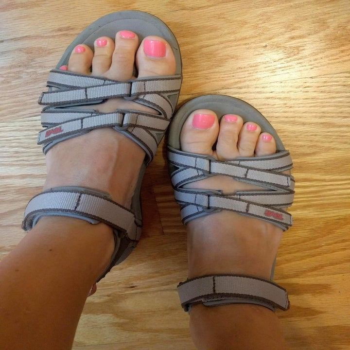 a reviewer photo of a pair of feet wearing gray Teva sandals
