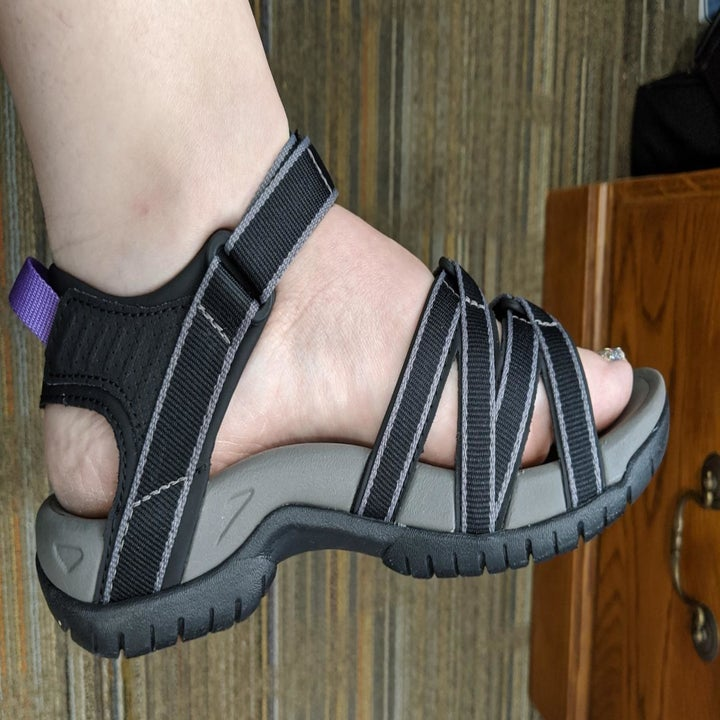 A reviewer photo of the profile view of a foot wearing the Teva sandal in black with gray trim