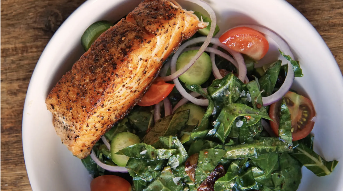 A plats of salad with a piece of fish