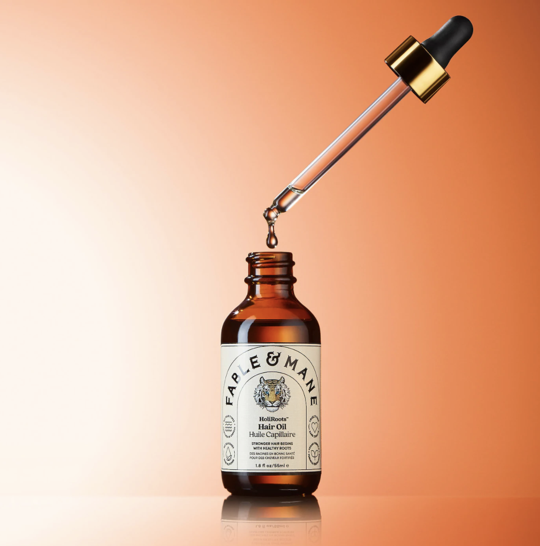 the bottle of the hair oil with a dropper on top