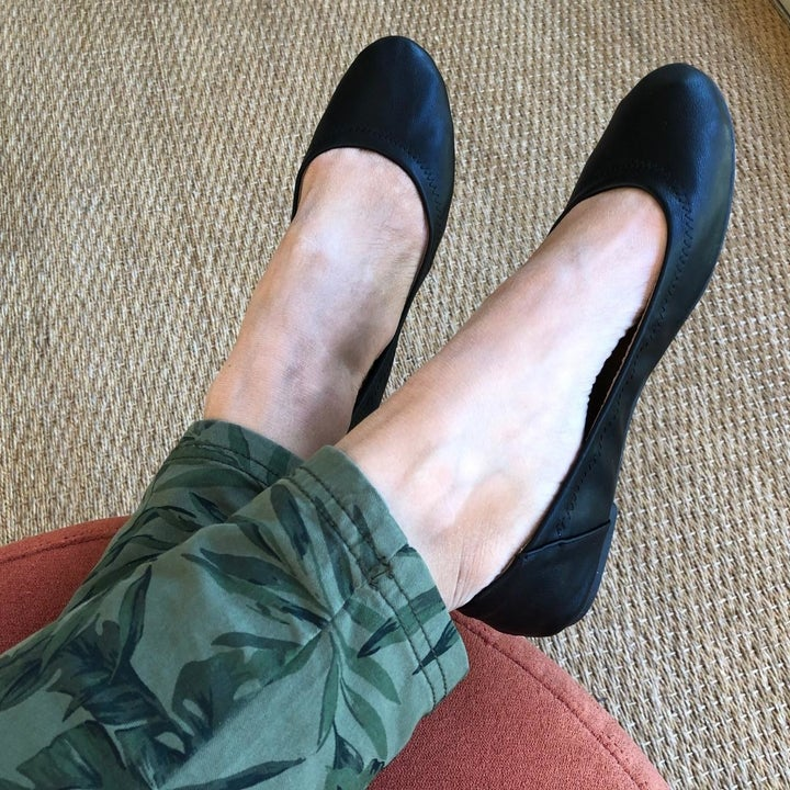 a reviewer photo of a pair of feet wearing green pants and black ballet flats