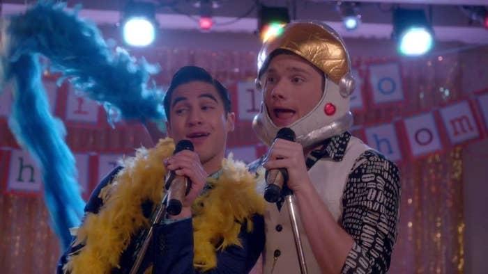 Kurt and blaine singing karaoke in feather boas and astronaut helmets