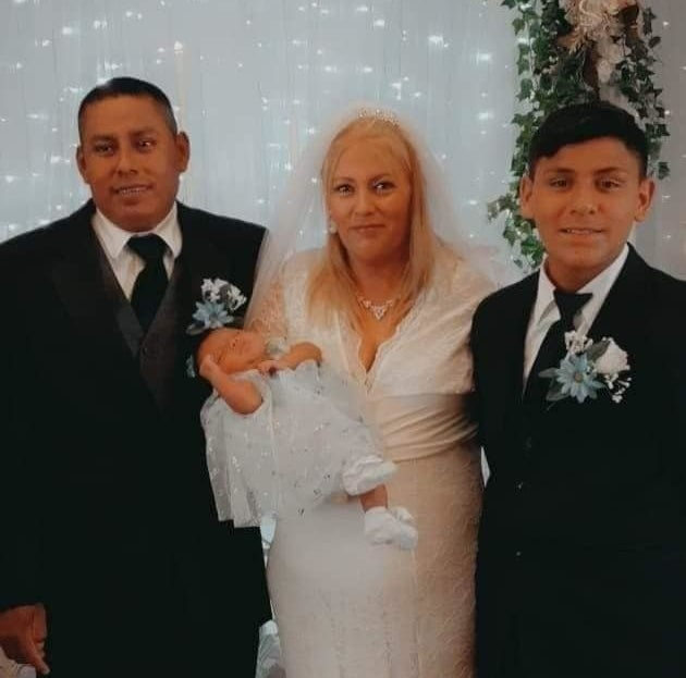 A bride in a white wedding dress and holding an infant stands between a boy and a man in suits and boutonnieres