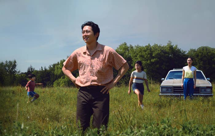 Steven Yeun's character stands in a field while his family plays around him.