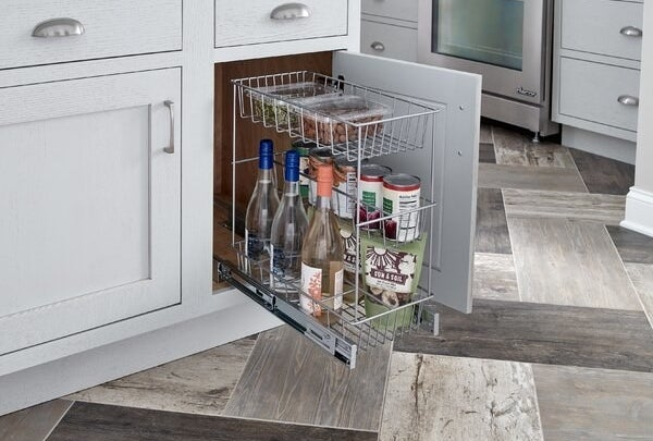 the pull out drawer holding wine bottles and canned goods