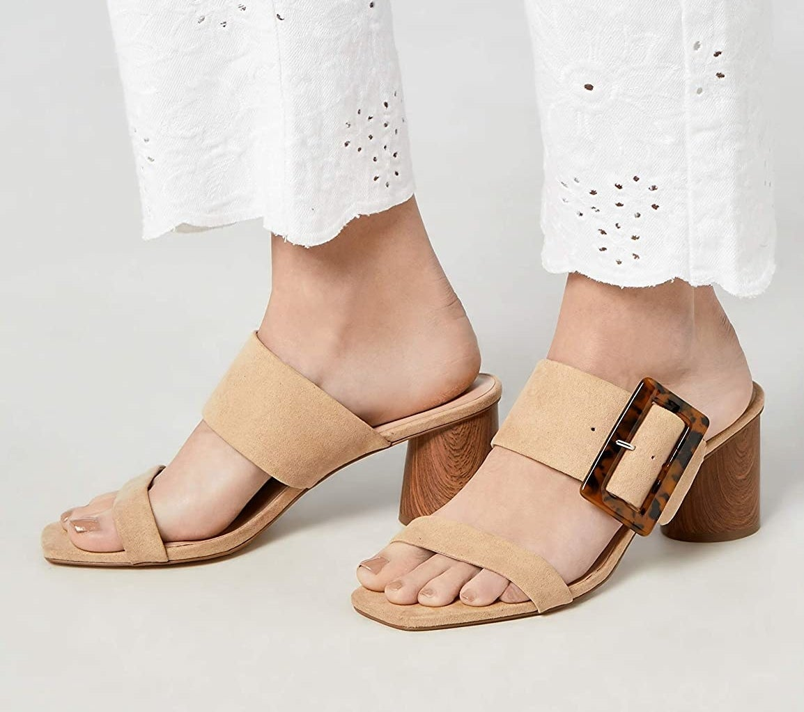 sandals being worn while standing with white pants