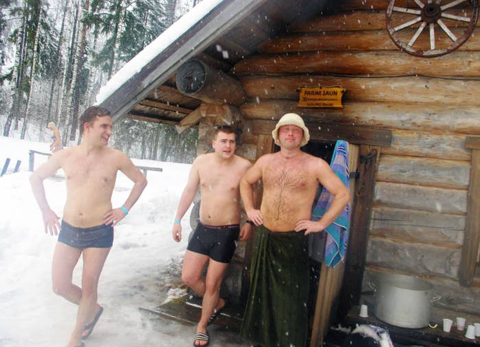 group of people wearing swimmers, walking out of a sauna into the snow