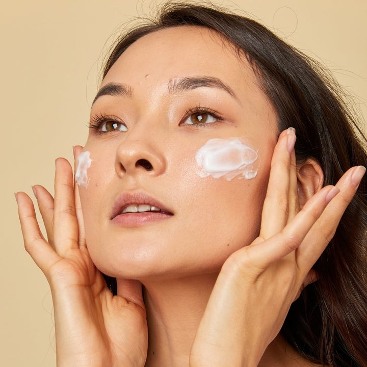 a model using foamy facial cleanser on their face
