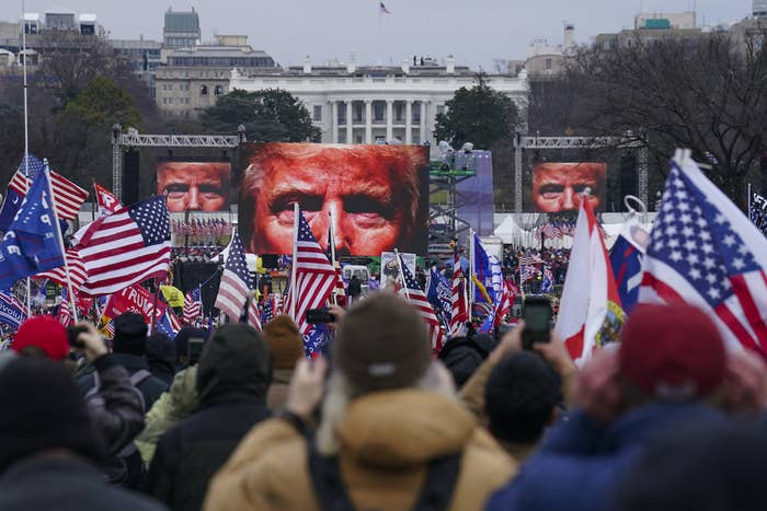 A close-up of Trump's eyes appear on three screens in the background before a crowd of people waving US and Trump flags